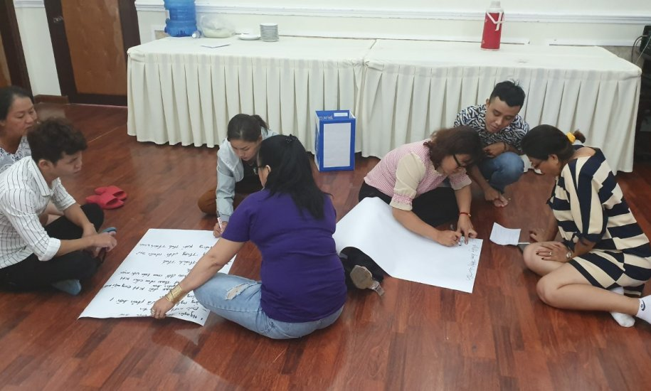 Sex worker activists doing group work around flip chart paper